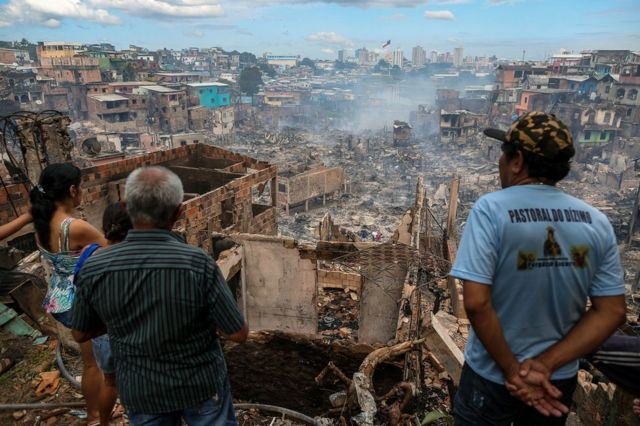 Residents look at the remains of Educandos neighbourhood the day after it was ravaged by a massive fire, in Manaus, Amazonas state, Brazil.