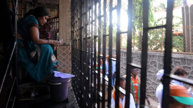 An Indian housewife reads an election pamphlet distributed by Bharatiya Janata Party (BJP) supporters outside her house during a campaign rally in Mumbai on April 10, 2014