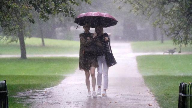 Two women walking in rain