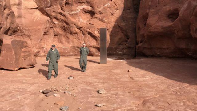 Pessoas caminham próximo ao monolito