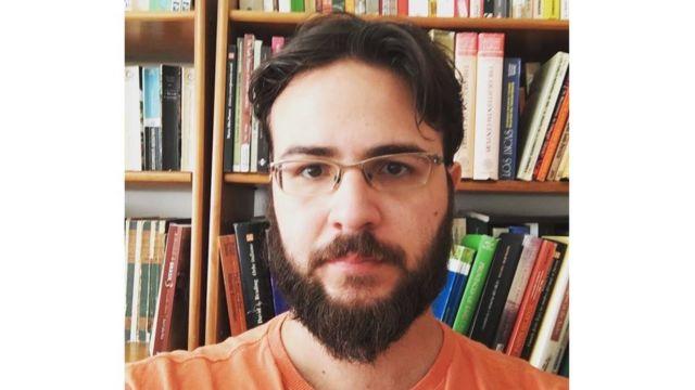 Foto de Krause em frente a estante de livros