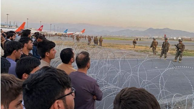 One picture showed Afghans crowding behind barbed wire near the airfield