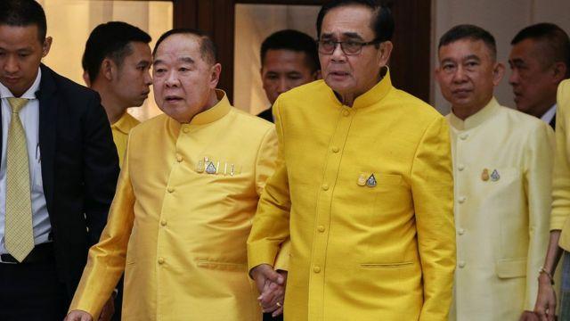 Prime Minister Prayuth Chan-ocha holds hands with Deputy Prime Minister and Defence Minister Prawit Wongsuwan