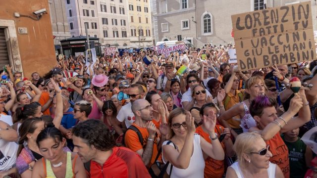 A large crowd has gathered in the streets, waving placards, in this daytime photograph taken within the mass of bodies