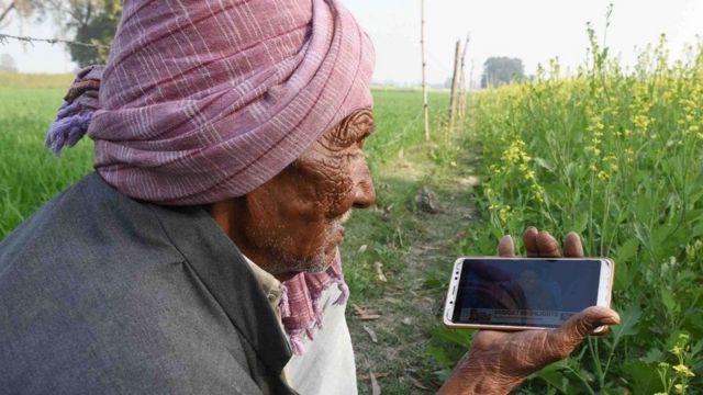 સ્માર્ટફોન વાપરતા એક વૃદ્ધ