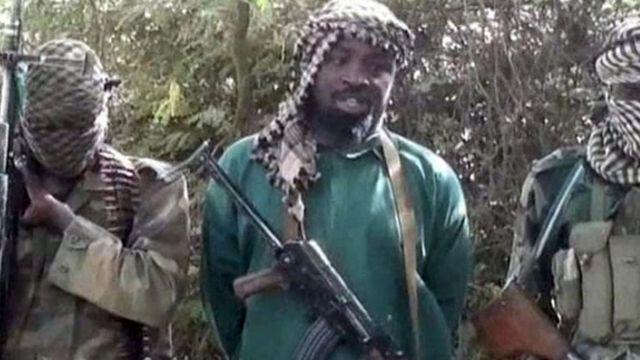 Abubukar Shekau stand between two militants wey hold machine gun.
