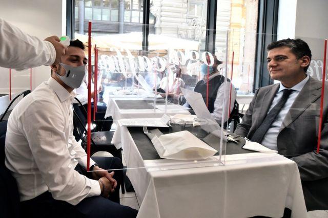 A waiter checks a customer's temperature in a restaurant