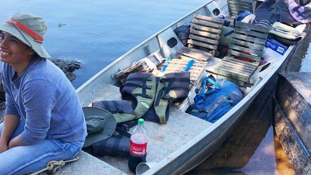 Maira Martinez durante un viaje de campo en un bote que contiene carpetas con plantas prensadas