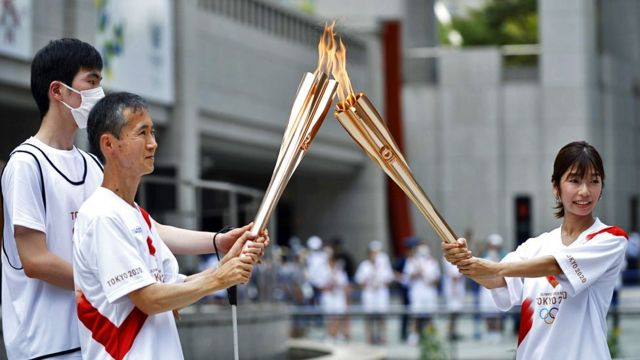 Torchbearers light the Olympic torch and pass the flame around to one another in Shinjuku District in Tokyo, Japan, on 23 July 2021