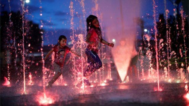 Niñas juegan en una fuente en Tapachula, México.