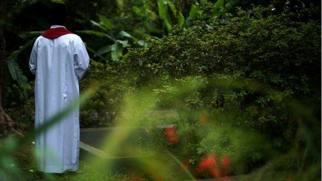 Un sacerdote de espaldas, vestido en alba blanca