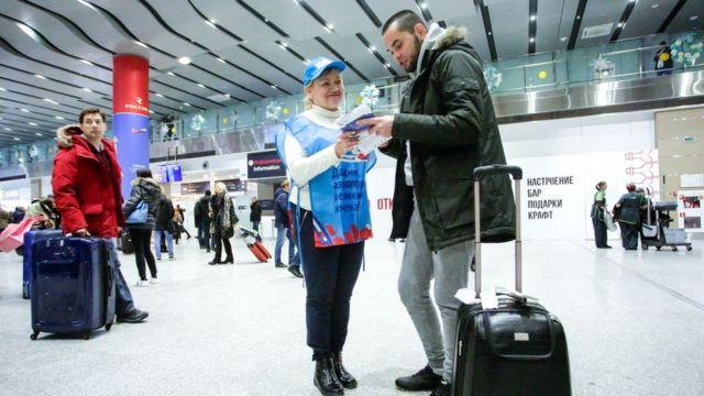 Сотрудница проекта дает карточк удля голосования пассажиру