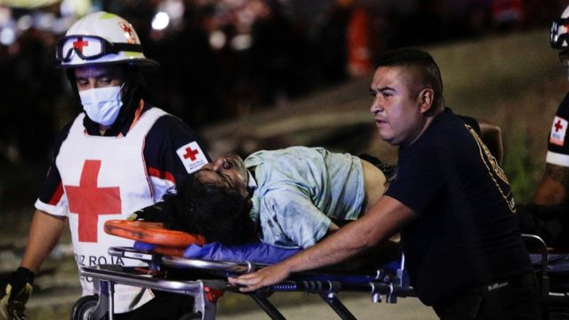 Rescue teams transport an injured person after the subway crash in Mexico City