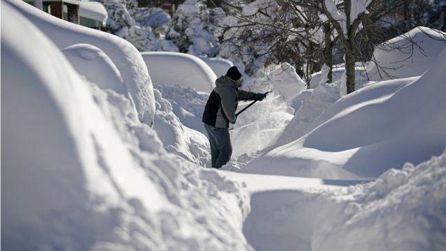 ニュージャージー州ユニオンシティで自宅玄関前の雪をかく男性(24日)