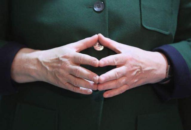 """El gesto de """"diamante"""" que la canciller alemana Angela Merkel suele hacer con las manos, uniendo las yemas de los dedos"""