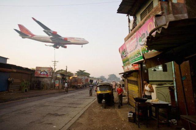 A man makes chapatis as an Air India passenger jet flies over the Jari Mari slum before landing at Mumbai Airport, on February 3, 2009 in Mumbai, India.