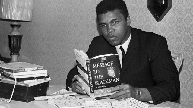 """Former heavyweight boxing champion Muhammad Ali reading the book """"Message to the Black Man."""""""