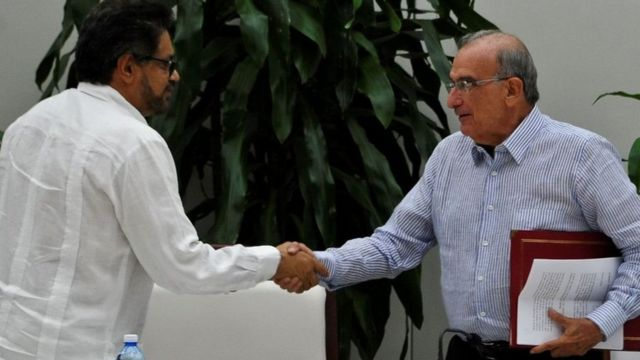 ممثل فارك إيفان ماركيز (يسارا) يصافح مفوض الحكومة أومبرتو دي لا كالي