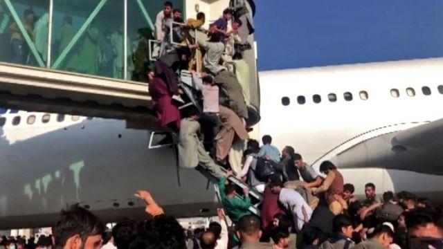 Pessoas se penduram a avião em Cabul