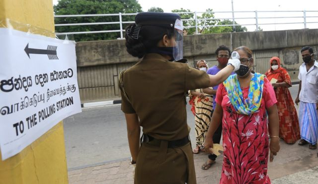 A Sri Lankan female police officer wearing a face mask conducts temperature checks as Sri Lankan voters wearing face masks stand in line during a mock election ahead of the parliamentary election in Colombo, Sri Lanka, on June 20, 2020.