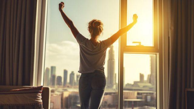 женщина потягивается на фоне окна