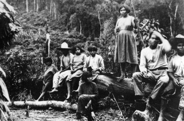 Indígenas sentados em pedaço de madeira