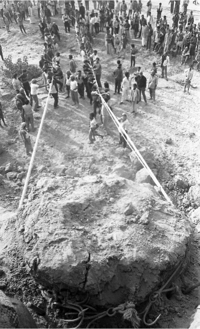 માટીના મોટા ઢગલાને ગબડાવવાનો પ્રયાસ કરતા લોકો