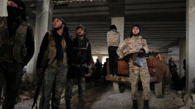أفراد من المعارضة المسلحة يحملون أسلحتهم داخل مبنى في مدينة حلب