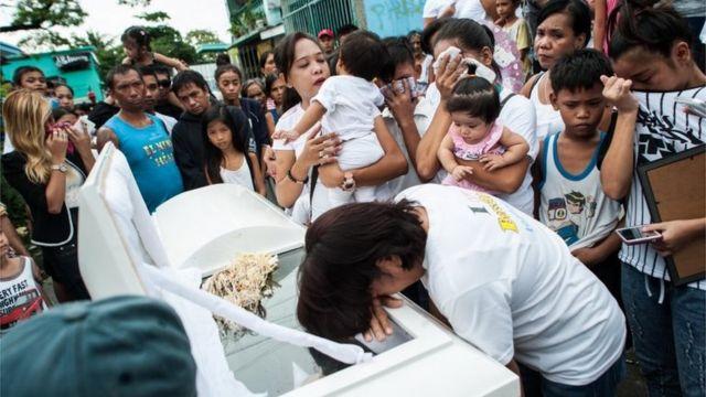 Parentes de uma vítima acusada de ser ladrão e traficante choram sobre o caixão durante um funeral