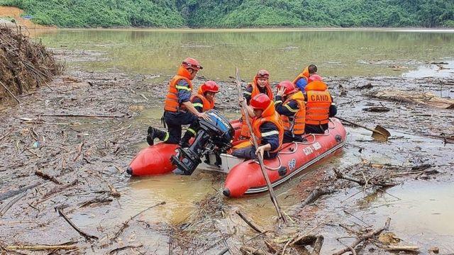 Các nhân viên tìm kiếm cứu nạn Việt Nam băng qua qua lòng hồ thủy điện Hương Điền tại xã Hương Bình, huyện Phong Điền để tìm kiếm các nạn nhân mất tích trong vụ sạt lở đất tại khu thủy điện Rào Trăng 3.