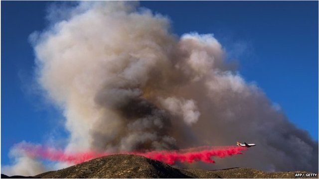 A plane drops bright red fire retardant on the Blue Cut wildfire in Lutle Creek, California