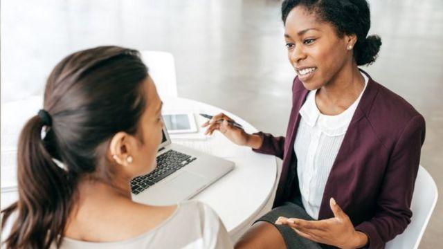 Duas mulheres conversando em uma reunião de trabalho