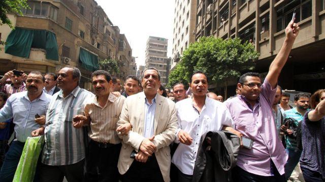 Le président du syndicat de la presse égyptienne Yahya Kallash, son secrétaire général et le chef du comité des libertés marche devant le palais de justice au Caire le 4 Juin 2016.