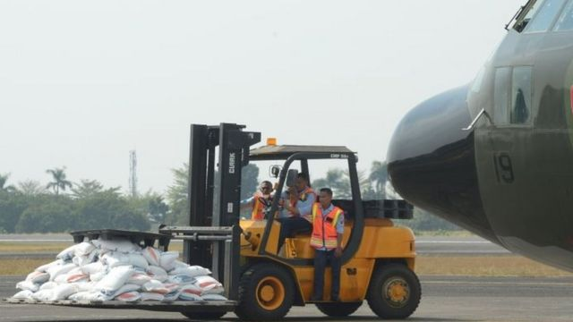 A forklift at the Halim Perdanakusuma airport in Jakarta ferries government food aid to an Indonesian air force C-130 aircraft bound for Bangladesh with its cargo for Rohingya refugees