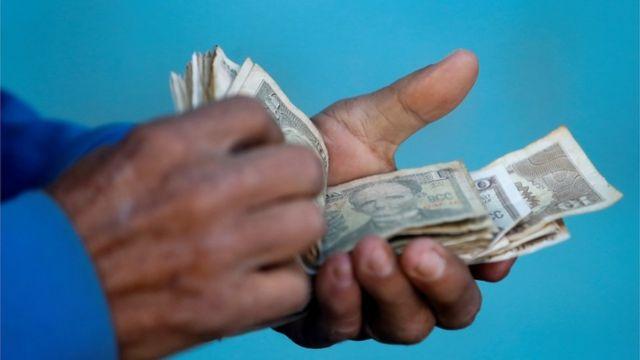Cubano maneja billetes.