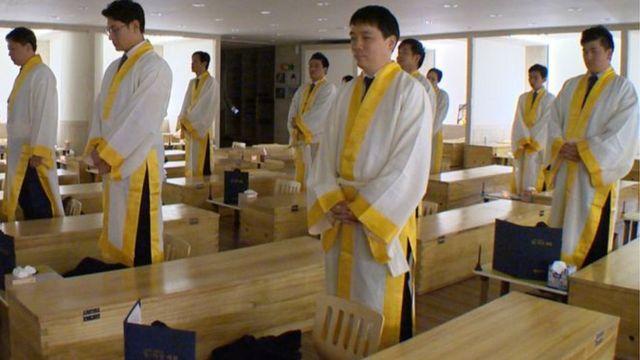 Pacientes del centro Hyowon de Seúl parados al lado de sus ataúdes de madera.