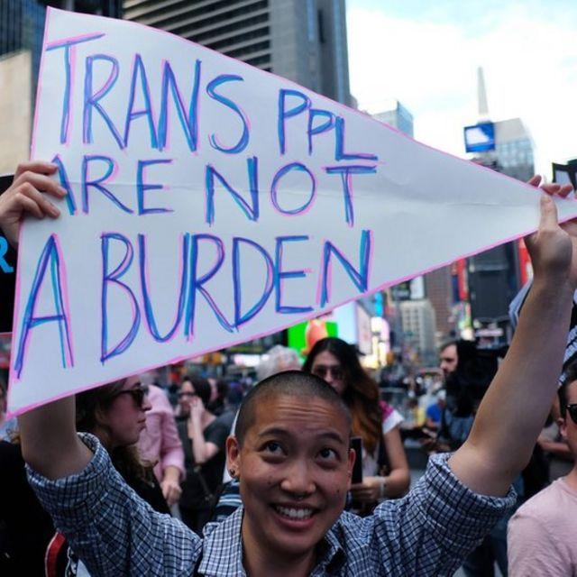"""Manifestante con cartel que dice: """"Las personas transgénero no son una carga""""."""