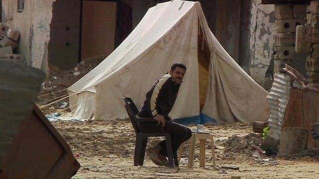 Man sits amongst rubble by tent