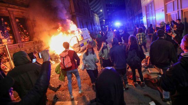 Protesters watch a police van burn