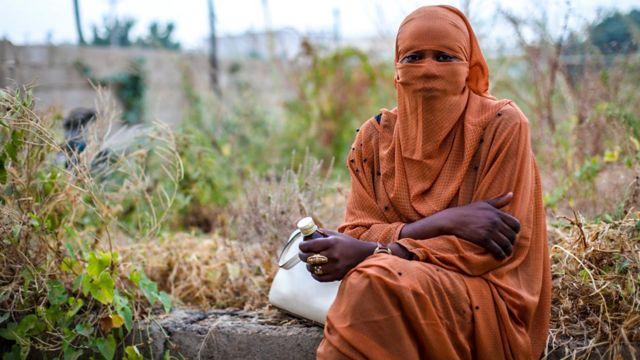 Mulher com hijab e xarope na mão