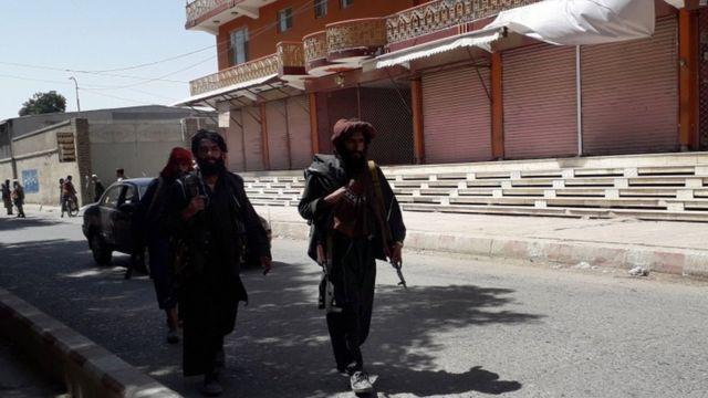 Três combatentes do Talebã caminham na rua, um deles com arma visível