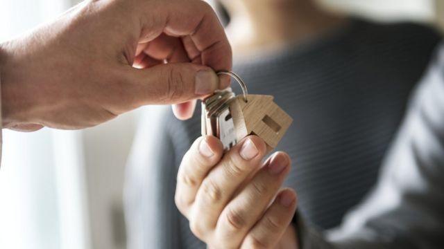 Persona recibe las llaves de una casa