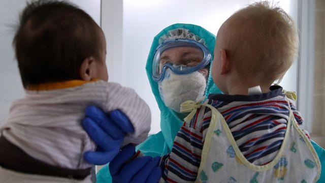Profissional da saúde interage com duas crianças