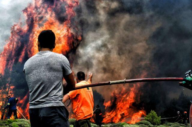Bomberos y voluntarios intentan extinguir las llamas de un incendio en la aldea griega de Kineta, cerca de Atenas, 24 de julio de 2018