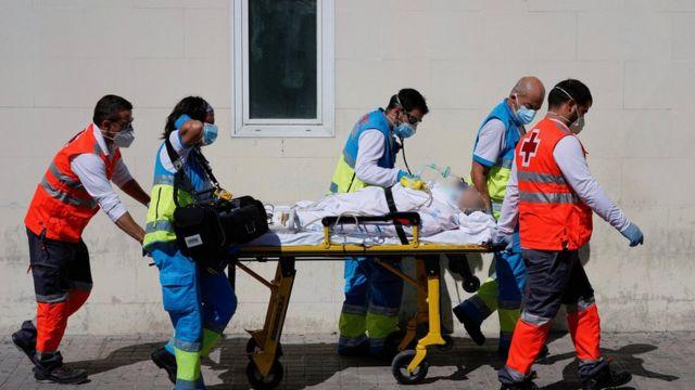 Trabajadores de la salud trasladan paciente en el hospital 12 de octubre.