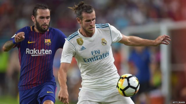 Gareth Bale of Real Madrid is challenged by Arda Turan of Barcelona