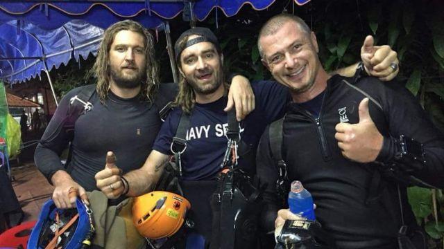 Erik Brown (esquerda), Mikko Paasi (centro) e Claus Rasmussen (direita) comemoram após o resgate ser concluído na Tailândia