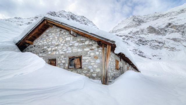 Una cabaña rodeada y cubierta de nieve