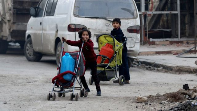 Children push containers in strollers as they flee deeper into the remaining rebel-held areas of Aleppo, Syria December 12, 2016