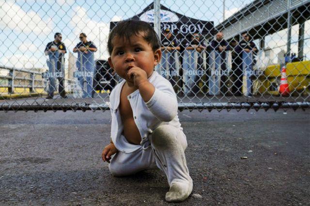 Годовалая мексиканская девочка перед пропускным пунктом на въезде в США.